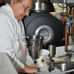 Martha bathing a puppy in the sink during a Groomathon at the rescue.
