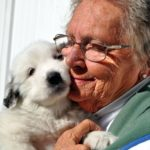 Martha hugging a Pyrenees puppy.